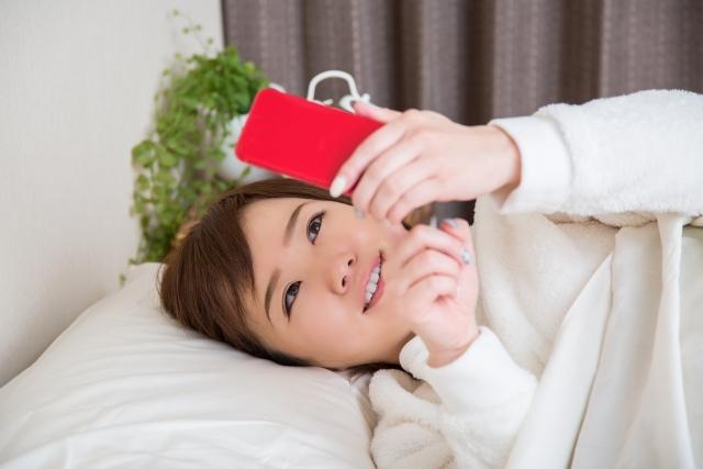 ベッドでスマホを操作する女性