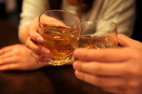 ウイスキーグラスで乾杯する男女